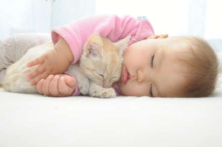 Photo pour Baby and cat sleeping together on white sheet - image libre de droit