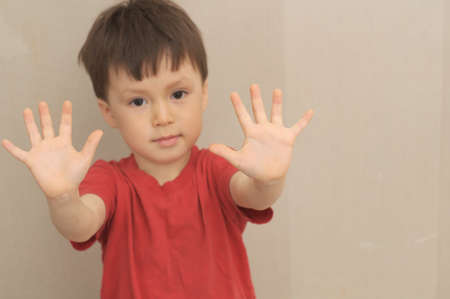 Boy with hands in front of himself like saying stop
