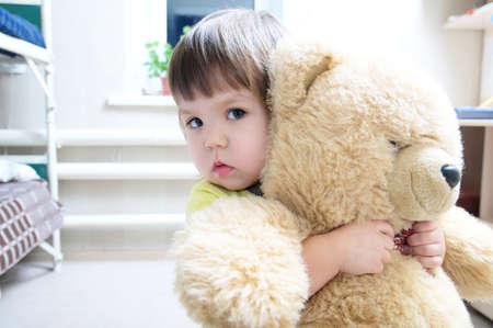 little girl hugging teddy bear indoor in her room, devotion concept, big bear toy