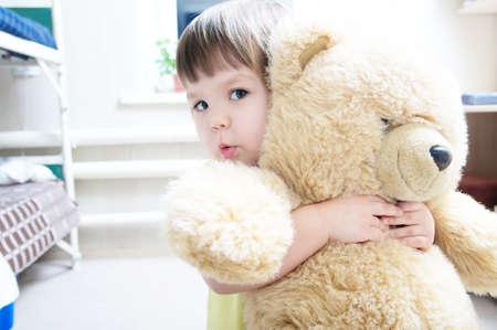 child hugging teddy bear indoor in her room, devotion concept,big bear toy