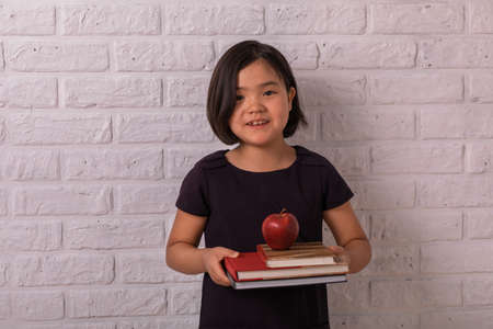 Photo pour Back to school. Little girl holds books and an apple near a white brick wall. Child from elementary school. Education. - image libre de droit