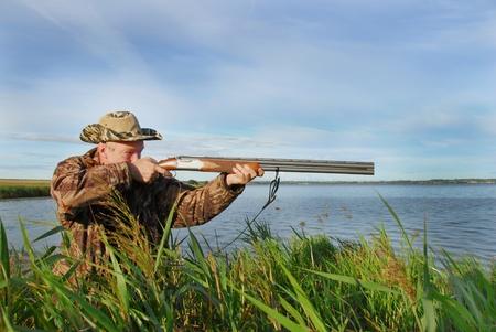 Duck hunter shoots his shotgun