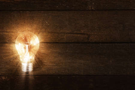 Glowing lightbulb on wooden background