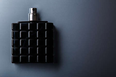 Black bottle of male perfume on metal surface