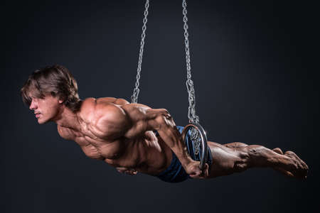 Strong and muscular gymnast guy on the rings