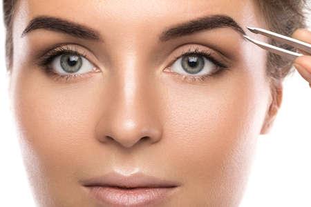 Foto de Close up of female face and eyebrow with tweezers - Imagen libre de derechos