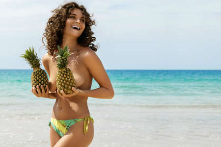 Beautiful woman with curly hair is holding pineapples  on the beach
