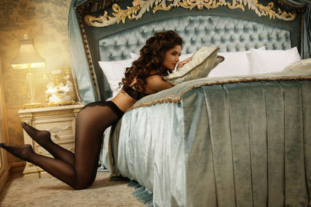 Photo for Sexy woman wearing a beautiful lingerie and a black tights in the luxury bedroom - Royalty Free Image