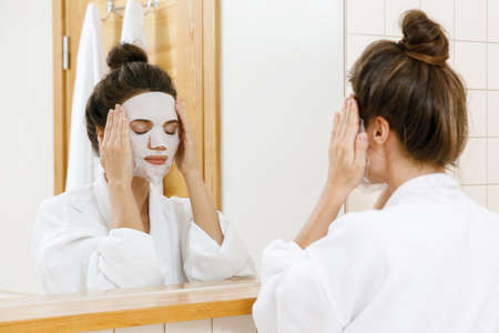 Photo pour Woman is applying sheet mask on her face in the bathroom - image libre de droit