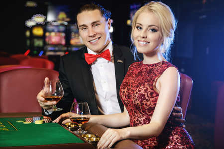 Foto de Beautiful well dressed couple playing roulette in the casino - Imagen libre de derechos