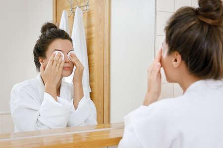 Foto de Woman removing makeup with a cotton pads - Imagen libre de derechos