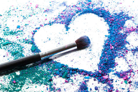 Photo for Crushed eyeshadows in shape of heart and make-up brushes - Royalty Free Image