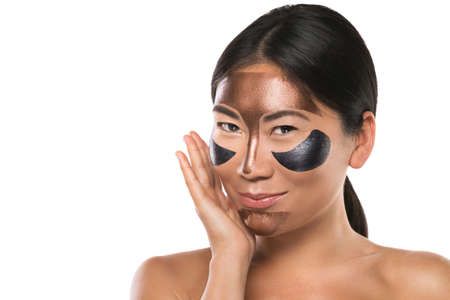 Photo pour Young Asian woman with peel-off mask on her face. Isolated on white background. - image libre de droit