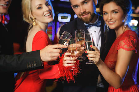 Photo pour Group of happy people during celebration is drinking sparkling wine in the casino - image libre de droit