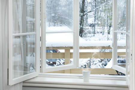Photo for Frosty and snowy day - Cup of hot drink on the windowsill. - Royalty Free Image