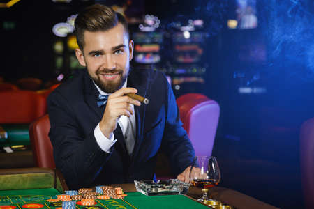 Photo pour Rich handsome man smoking cigar and playing roulette in the casino - image libre de droit