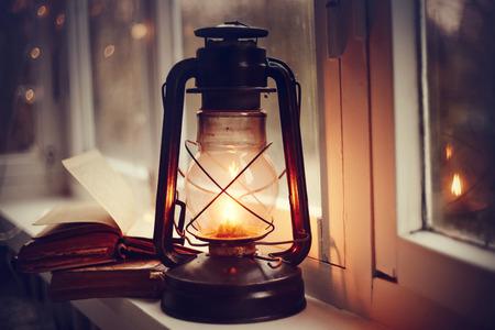 Photo for Kerosene lamp and old books on the windowsill. - Royalty Free Image