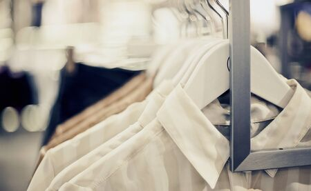 Photo pour Shirts on hangers. Shopping in store. Clothes on hangers in shop for sale. Blur background. Fashionable clothes in a boutique. Various clothing on market. - image libre de droit