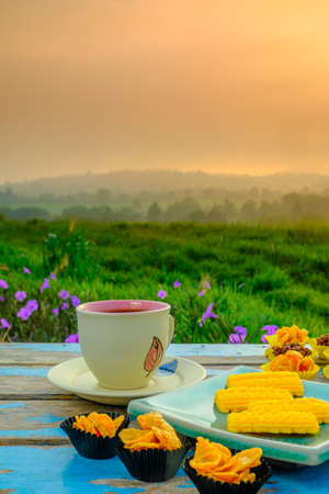 Photo for Black coffee cup, a Malay traditional cookies called Kuih Semperit , honey cornflakes cup, chocolate almond and florentine cookies  on wooden table over blurred image of beautiful scenery. - Royalty Free Image