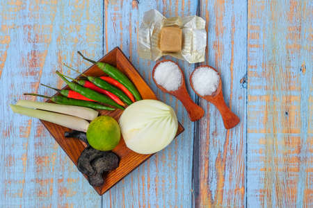 Photo pour Wooden plate with salt, msg,ginger,garlic,onion,key lime, chilies, chicken stock cube,  and lemongrass over the wooden cutting board. - image libre de droit