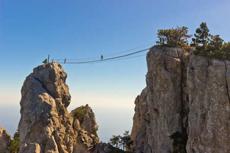 People crossing the chasm on the hanging bridge. Black sea background, Crimea, Russia