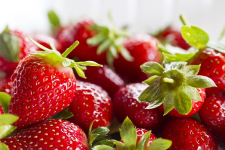 Foto de close up view of bunch of strawberries on white plastic plate with natural lighting - Imagen libre de derechos