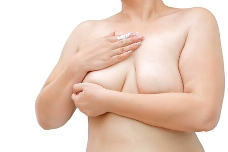 Photo for a woman with overweight and saggy Breasts smears cream on the chest - Royalty Free Image