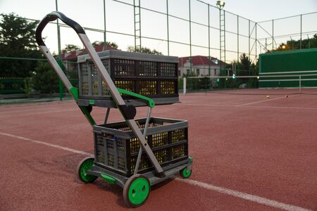 Foto per trolley for tennis balls on the tennis court in the evening - Immagine Royalty Free