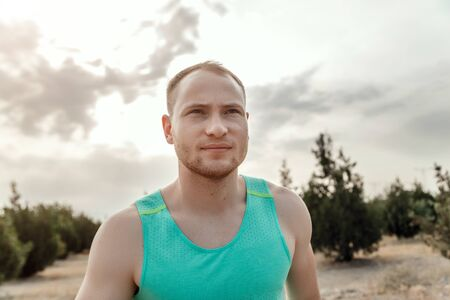 Foto per Caucasian guy in a blue t-shirt and black shorts, running over rough terrain. training during sunset - Immagine Royalty Free
