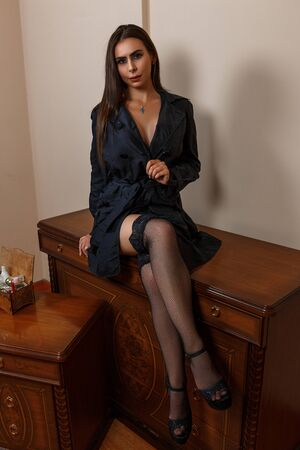 Foto de beautiful Caucasian woman housewife wife in black raincoat and beautiful lingerie sitting on the dressing table at home - Imagen libre de derechos