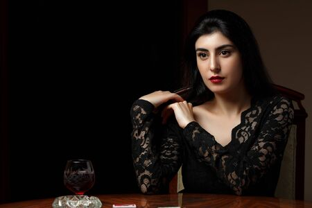 Photo pour a beautiful brunette woman with scarlet lips in black clothes sits at a table and undresses after losing at cards - image libre de droit
