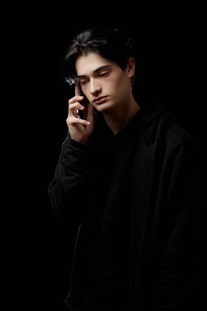 Photo pour young guy in a black hoodie on a black background with a mobile phone in his hands - image libre de droit