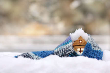Photo pour small wooden house in a warm blue scarf in covered with snow / property insurance against natural phenomena - image libre de droit