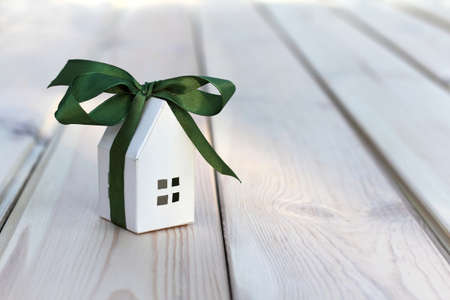 Photo for White paper house layout wrapped in green ribbon with bow. small gift great holiday - Royalty Free Image