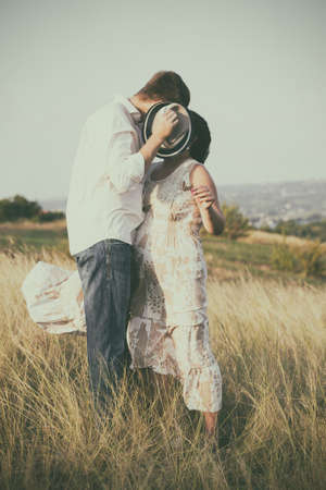 a boy and a girl kissing a hat closing faceの写真素材