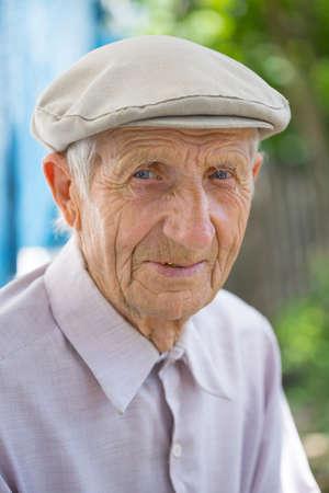 Foto de portrait of  senior man sitting near his house in the village  - Imagen libre de derechos