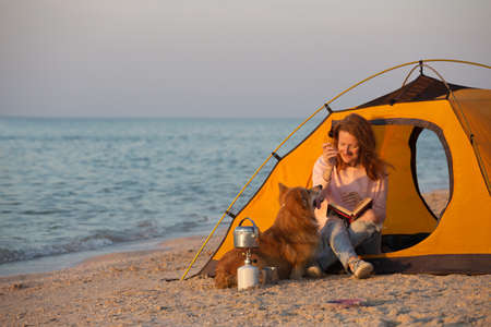 Photo pour happy weekend by the sea - smiling girl with a dog in a tent on the beach at dawn. Ukrainian landscape at the Sea of Azov, Ukraine - image libre de droit