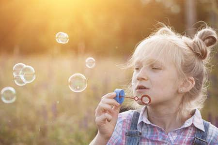 Photo pour happy summer - girl blowing bubbles outdoors - image libre de droit