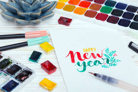 girl makes the inscription watercolor -  happy New Year