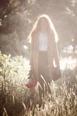 Foto per girl walking in the field at sunset light - Immagine Royalty Free
