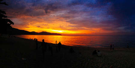 Sunset over the ocean with silhouette of people at the beach panorama. Beautiful golden glow spread across the sky as the sun chased the dark clouds away.の写真素材