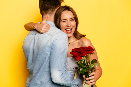 Foto de Attractive young woman with red roses winking and showing a thumb while hugging her boyfriend. Celebrating St. Valentine's Day. - Imagen libre de derechos