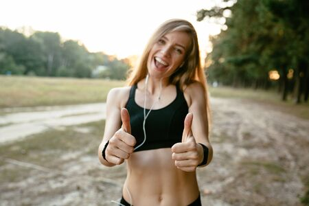 Photo for Summer portrait of sportive girl in tank top, showing a thumb up, cheerfully smiling and looking at camera. Workout outside. - Royalty Free Image