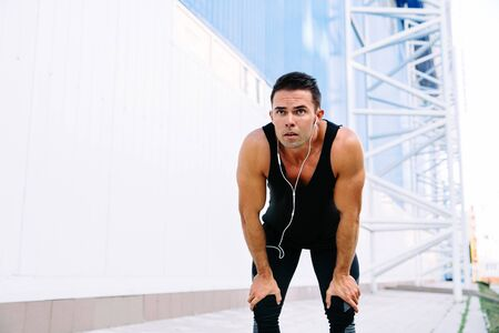 Photo pour Handsome muscular man in headset resting after running, during workout outdoors, wearing black sportswear. - image libre de droit