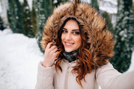 Foto de Winter selfie. Beautiful girl in fur hood takes selfie in snowy winter day - Imagen libre de derechos