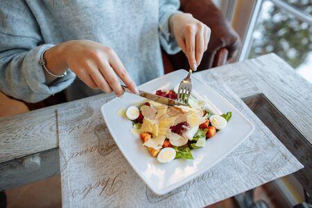 Photo pour Woman eats a delicious Caesar salad in a restaurant. Closeup - image libre de droit
