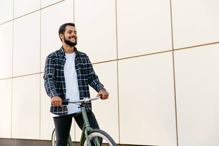 Photo pour Outdoor photo of cheerful bearded man riding a bicycle , spending time with pleasure, wearing stylish clothes. - image libre de droit