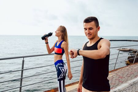 Photo for Happy muscular guy checking a cardio and time after running, while a fitness girl drinking a water after running a distace. Outdoors, near the ocean. - Royalty Free Image
