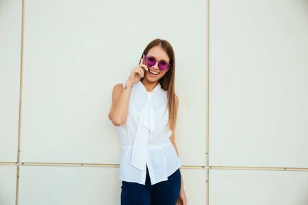 Joyful young woman having pleasant conversation by mobile phone, laughing cheerfully, wearing sunglasses, standing against the modern wall. Outdoors.の写真素材