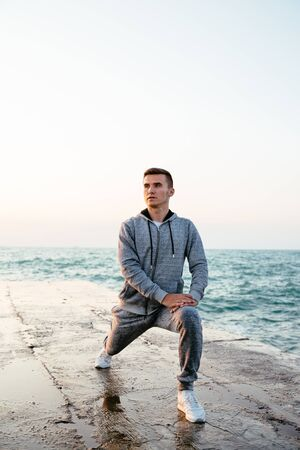 Photo for Attractive concentrated guy in sportswear doing exercises for legs, stretching on pier, near the sea. Outdoors. - Royalty Free Image